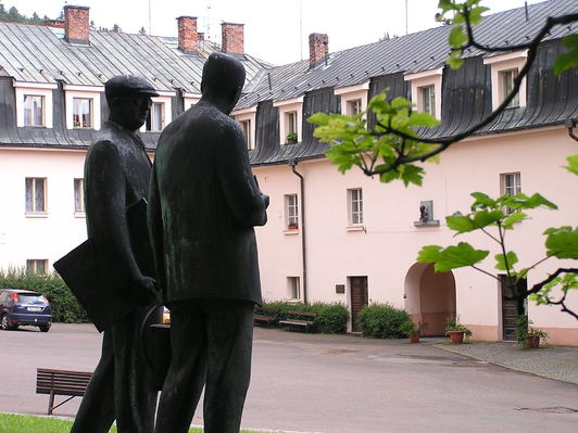 A sculpture of the Čapek brothers with their native house in the background, currently a museum